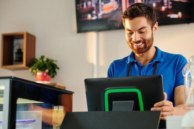 Barista barbuto sorridente che lavora sul terminale pos quando si inserisce l'ordine del cliente o si accetta il pagamento