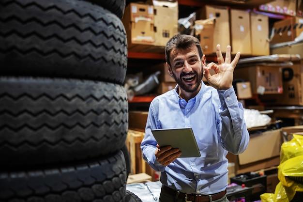 Sorridente uomo d'affari eccitato barbuto in piedi in deposito di azienda di esportazione, tenendo tablet e mostrando segno giusto.