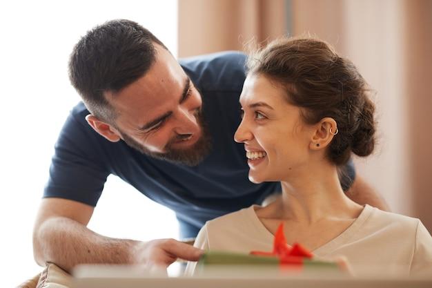 Uomo barbuto sorridente che dà una confezione regalo alla bella ragazza mentre si congratula con lei per l'anniversario o ...