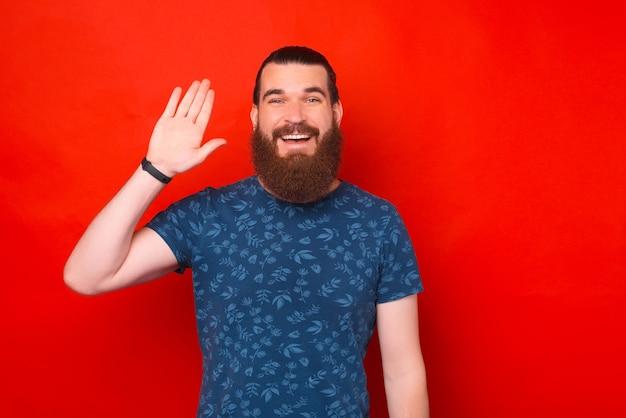 L'uomo barbuto sorridente si presenta salutando e salutando.