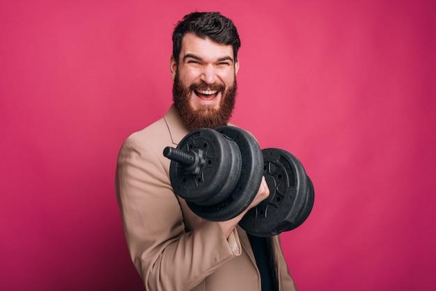 L'uomo barbuto sorridente sta sollevando un dummbel sul rosa.