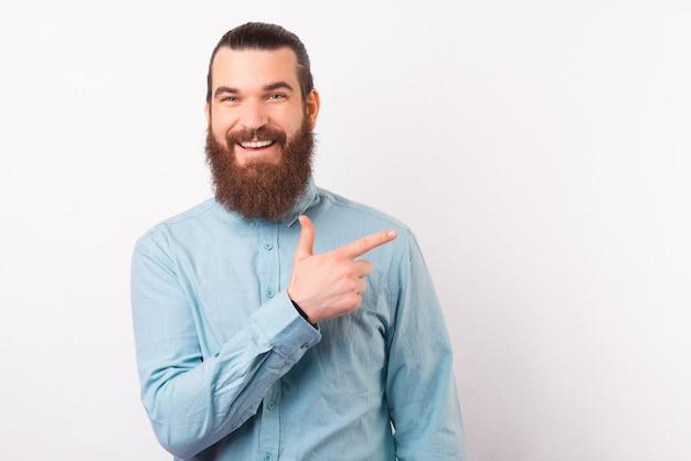 L'uomo barbuto sorridente sta indicando da parte su fondo bianco.
