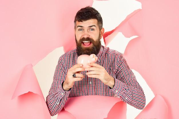 Uomo barbuto sorridente che guarda attraverso il foro e tiene il concetto di affari del salvadanaio risparmiando denaro concept