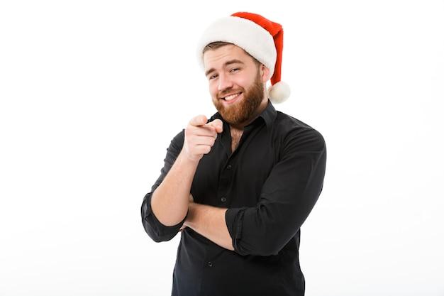 Sorridente uomo barbuto in camicia e cappello di natale