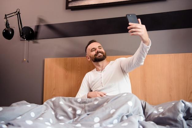 Uomo barbuto sorridente in pigiama bianco seduto a letto e facendo selfie sullo smartphone dopo il risveglio