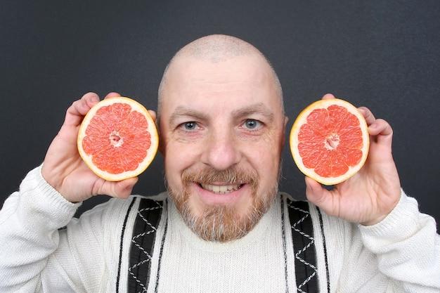 Uomo barbuto sorridente con un pompelmo tagliato nelle sue mani