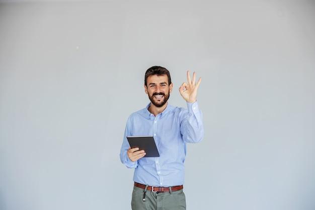 Sorridente giovane ceo barbuto in piedi davanti a uno sfondo bianco, tenendo tablet e mostrando segno ok mentre guarda la fotocamera