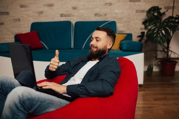 Sorridente giovane barbuto sta utilizzando il computer portatile, seduto in accogliente poltrona rossa a casa. felice maschio in chat nei social network e mostra il segno cool.