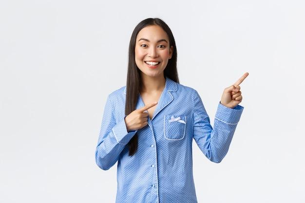 Sorridente bella ragazza asiatica in pigiama blu che fa annuncio, puntando le dita nell'angolo in alto a destra per mostrare grandi notizie o banner promozionale, consiglia la pubblicità sul muro bianco
