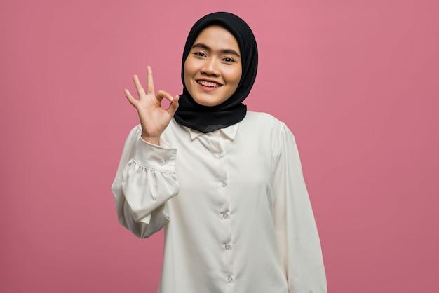 Bella donna asiatica sorridente che mostra segno giusto