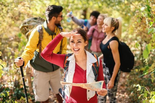 Bella mappa castana sorridente della tenuta e condurre il resto delle viandanti attraverso il legno in autunno.
