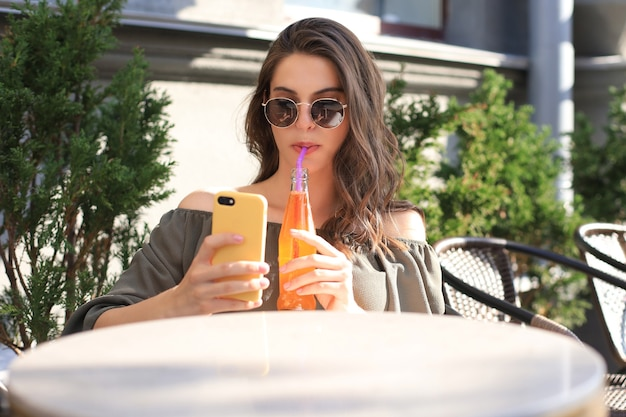 Sorridente bella donna bruna seduta in un caffè estivo di strada, prendere selfie con il cellulare, bere succo di frutta.