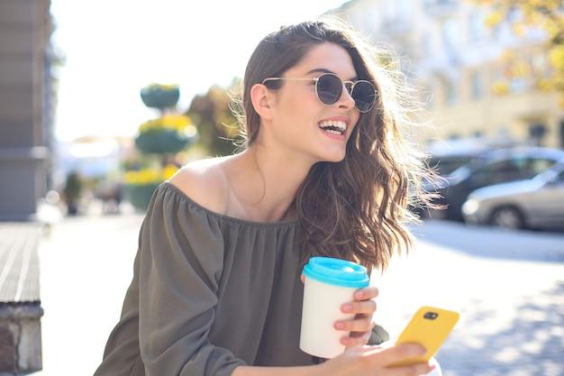 Sorridente bella donna bruna che cammina all'aperto per strada, scatta selfie con il cellulare, bevendo caffè.