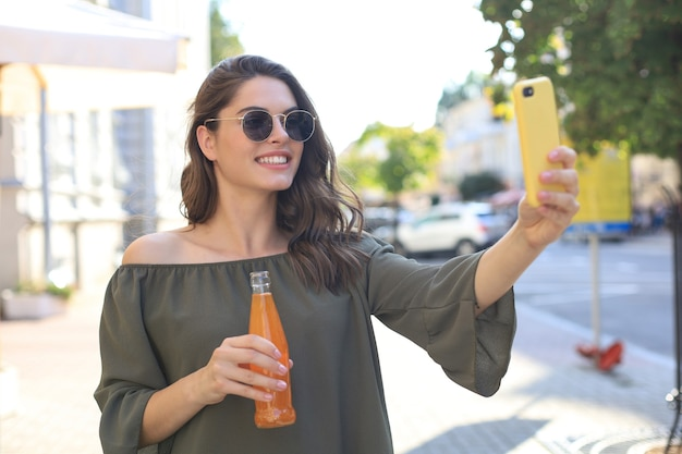 Sorridente bella donna bruna che cammina all'aperto per strada, scatta selfie con il cellulare, bevendo succo di frutta.