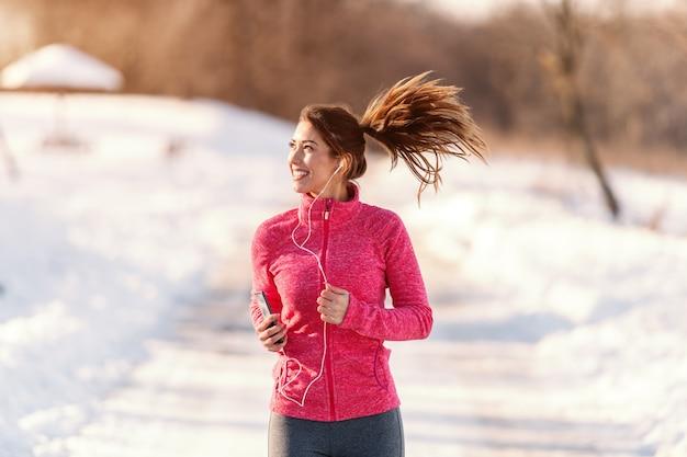 Bella donna caucasica sorridente in abiti sportivi che funzionano sul tempo nevoso e che ascoltano la musica. inverno, concetto di stile di vita sano.