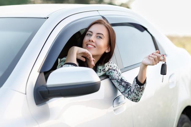 La bella ragazza sorridente in macchina tiene le chiavi