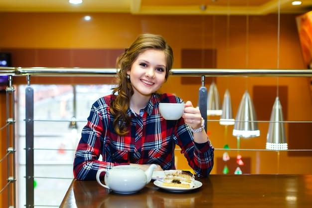 Bella ragazza sorridente in una camicia a quadri che beve tè in un caffè
