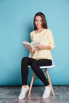 Sorridente bella ragazza che legge un libro e si siede su una sedia isolata sullo sfondo blu
