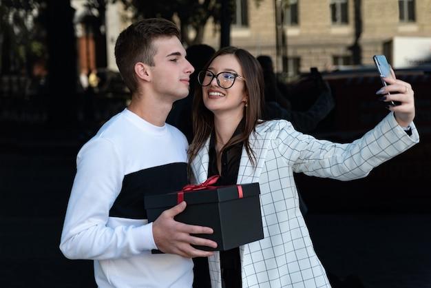 La bella ragazza sorridente prende un selfie con il suo ragazzo. il ragazzo fa un regalo alla ragazza. coppia felice ad un appuntamento.