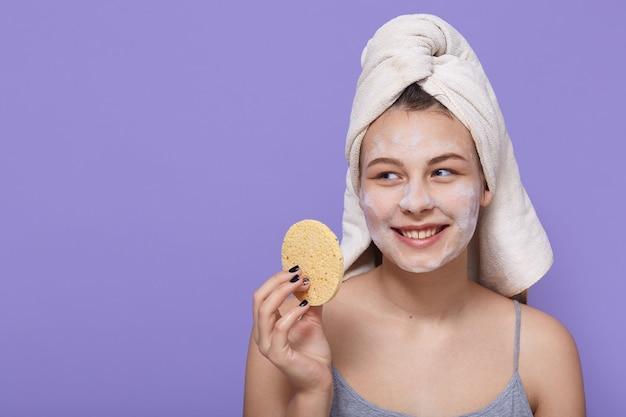 Sorridente bella signora che guarda lontano con felice espressione, tenendo la spugna nelle mani e la maschera cosmetica sul viso su lilla