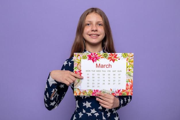 Sorridente bella bambina sulla tenuta del giorno della donna felice e indica il calendario isolato sulla parete blu