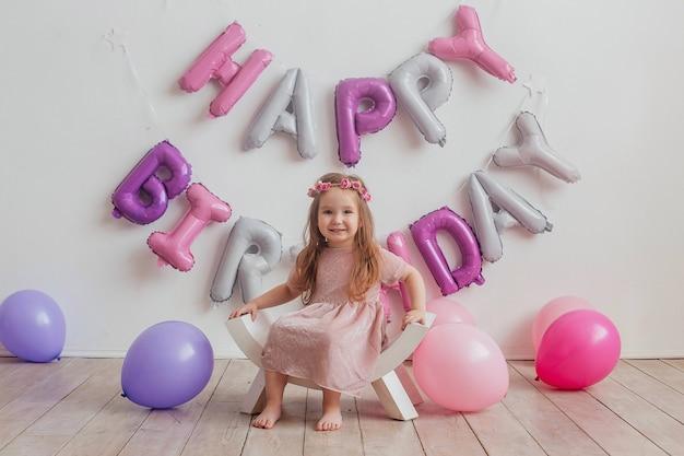 Sorridente bella bambina con i capelli lunghi su uno sfondo bianco con palloncini, copia dello spazio