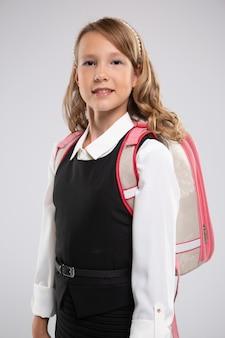 Bella scolara sorridente con una borsa dello studente