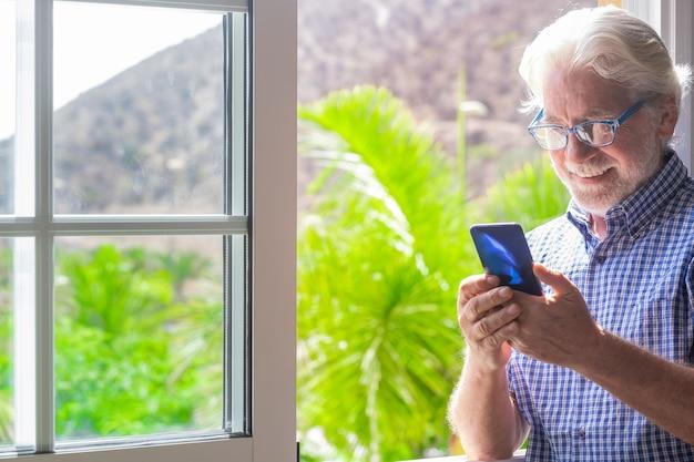 Sorridente bellissimo uomo anziano alla finestra usando il cellulare