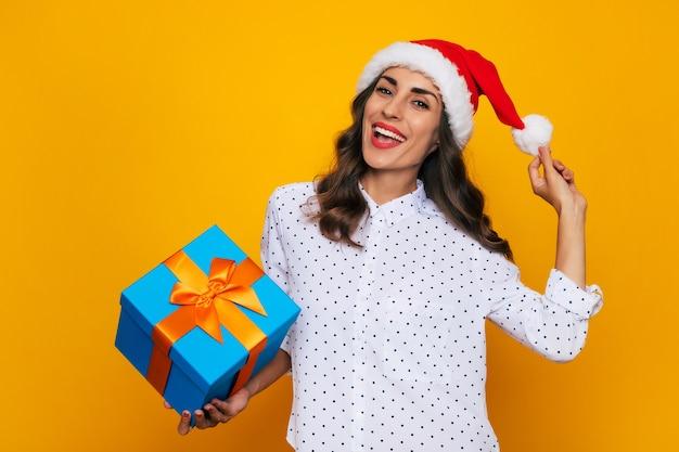 La bella donna sorridente in un cappello rosso di santa con una scatola regalo in mano sta posando sullo sfondo giallo isolato mentre celebra il natale e il nuovo anno