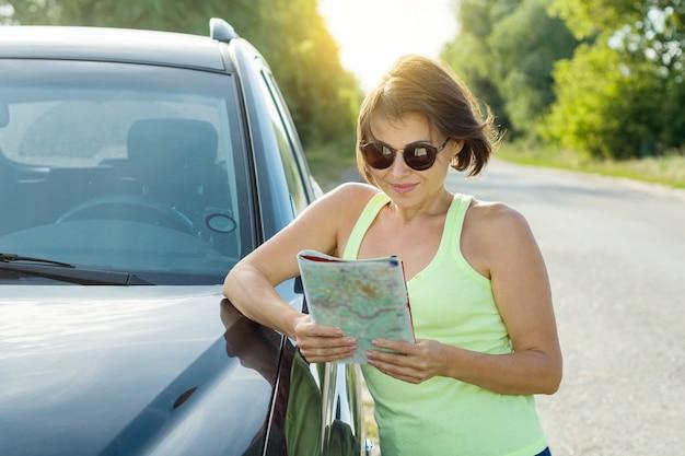 Bello viaggiatore sorridente della donna che esamina la mappa turistica