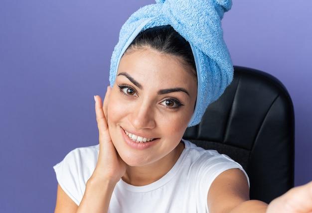Bella donna sorridente con i capelli avvolti in un asciugamano che mette la mano sulla guancia