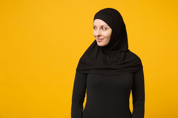 Sorridente bella giovane donna musulmana araba in abiti neri hijab che guarda da parte la telecamera isolata sulla parete gialla, ritratto. concetto di stile di vita religioso della gente.
