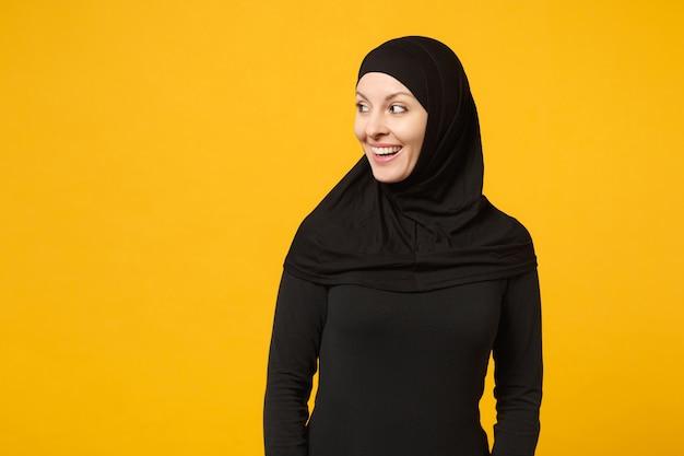 Sorridente bella giovane donna musulmana araba in abiti neri hijab che guarda da parte isolata sulla parete gialla, ritratto. concetto di stile di vita religioso della gente.