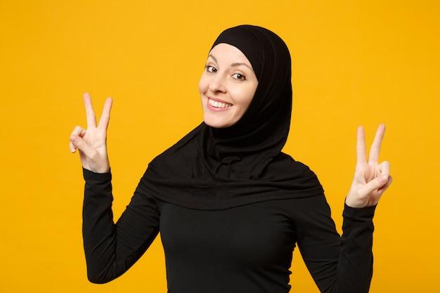 Sorridente bella giovane donna musulmana araba in abiti neri hijab che mostrano segno di vittoria isolato sul ritratto giallo della parete. concetto di stile di vita dell'islam religioso della gente.