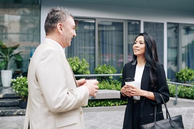 Sorridente bella giovane imprenditrice asiatica ascoltando le idee del suo collega senior quando stanno bevendo prendere il caffè all'aperto