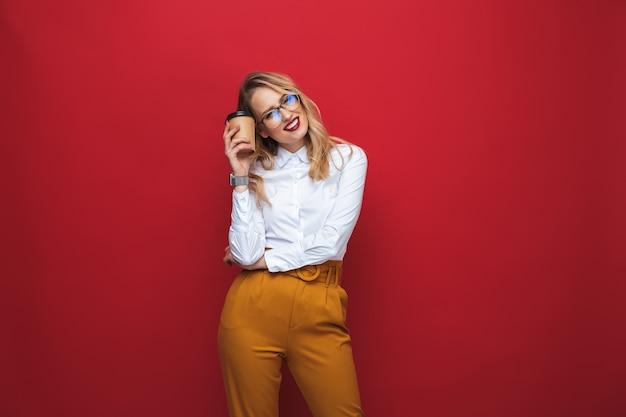 Sorridente bella giovane donna bionda in piedi isolato su sfondo rosso, tenendo la tazza di caffè da asporto