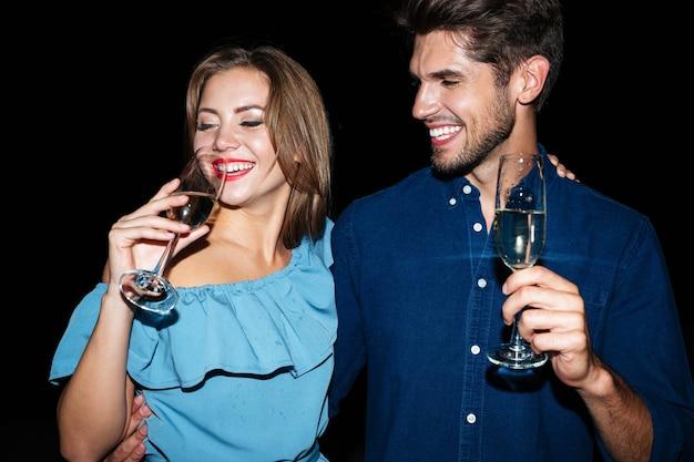 Sorridente bella giovane coppia in piedi e bevendo champagne di notte insieme