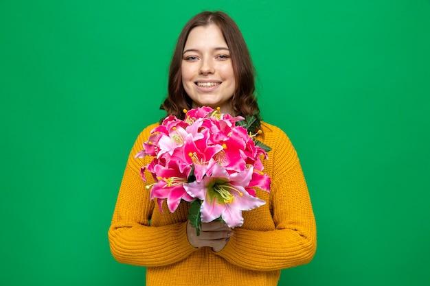 Bella ragazza sorridente il giorno della donna felice che tiene il mazzo isolato sul muro verde Foto Premium