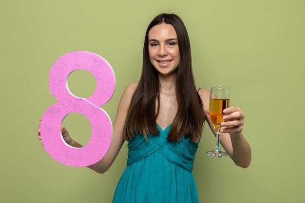 Sorridente bella ragazza il giorno della donna felice tenendo il numero otto con un bicchiere di champagne