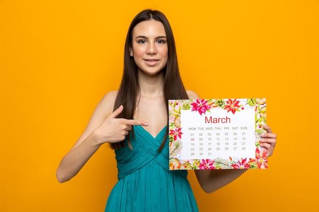 Bella ragazza sorridente sulla tenuta della festa della donna felice e punti al calendario