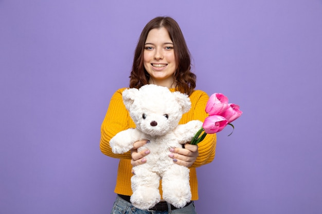 Bella ragazza sorridente che porge fiori con l'orsacchiotto