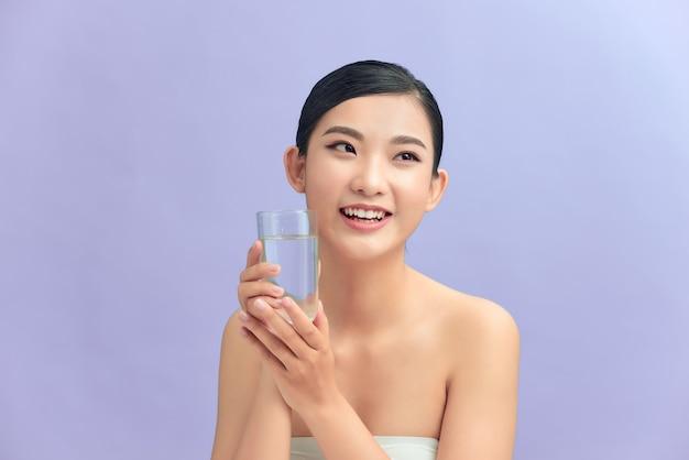 Bella giovane signora sorridente che tiene un bicchiere di acqua potabile. isolato nel colore di sfondo.
