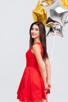 Sorridente bella giovane donna in abito rosso in piedi e tenendo palloncini a forma di stella su sfondo bianco