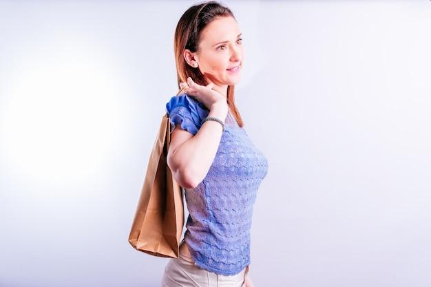 Sorridente bella giovane donna con un sacchetto di carta dietro la schiena. concetto di acquisto sostenibile. senza plastica