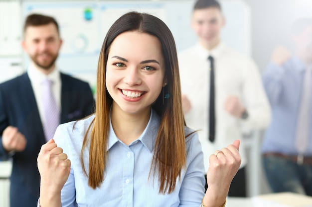 Ritratto sorridente dell'ufficio della donna di affari di bellezza che si leva in piedi sul fondo della gente di affari del gruppo. dimostra la gioia di vincere il periodo di rendicontazione degli affari di completamento dell'istruzione e il concetto di energia