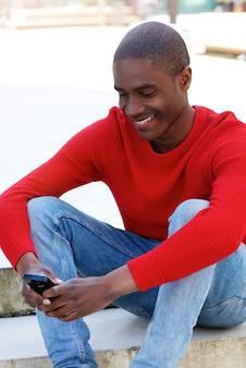 Uomo di colore sorridente seduto fuori utilizzando il cellulare