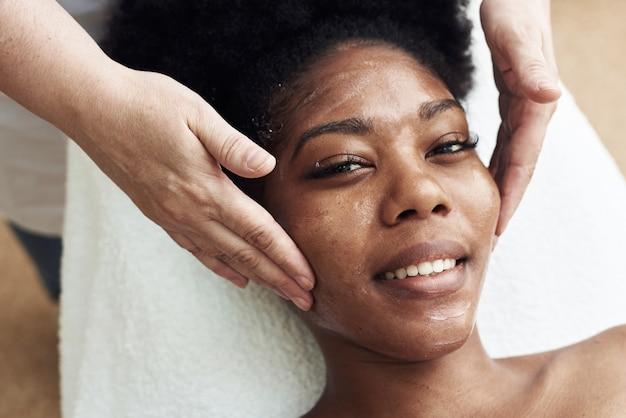 Donna nera sorridente che gode di un massaggio facciale tonificante. serena donna rilassante all'aperto
