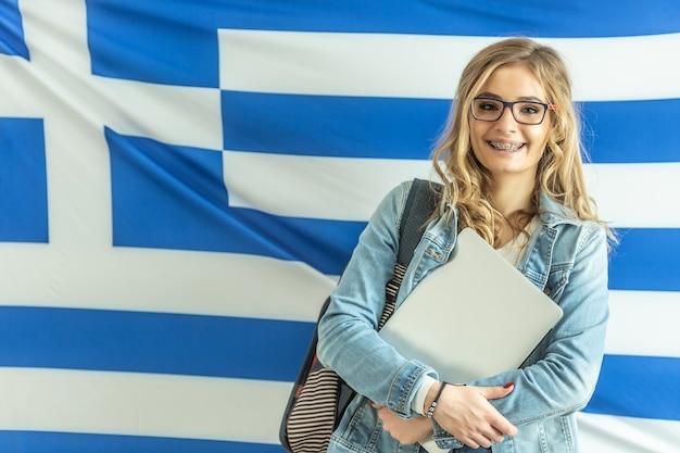 Sorridente studentessa bionda che indossa bretelle si trova di fronte alla bandiera della grecia.