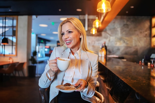 Bionda sorridente in abiti da cerimonia seduto in un bar di un hotel di lusso, bevendo caffè e aspettando il check-in.
