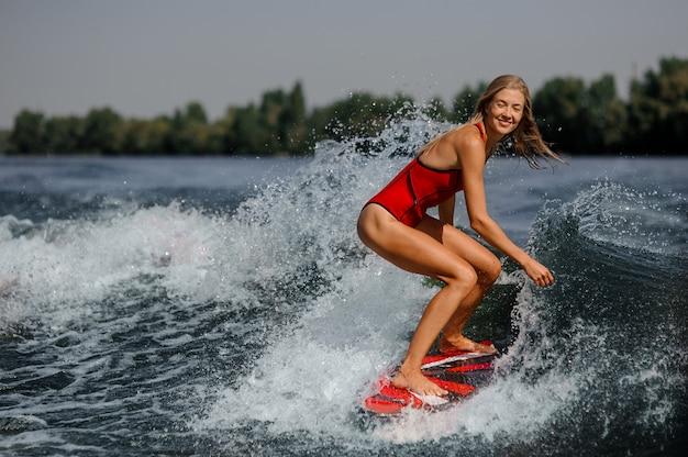Ragazza bionda sorridente che guida sul wakeboard rosso